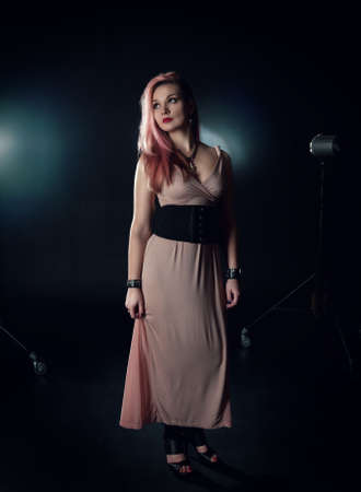 Beautiful young woman with pink hair posing in photo studio photo