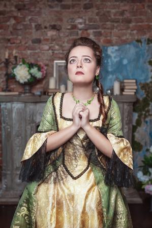 middeleeuwse jurk: Bidden mooie vrouw in middeleeuwse kleding in de oude kamer Stockfoto