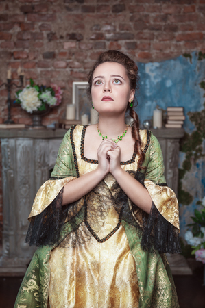 Praying beautiful woman in medieval dress in the old room photo