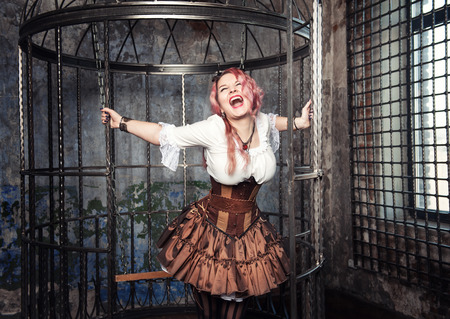 Screaming beautiful steampunk woman with pink hair sitting in the metal cage