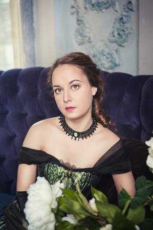middeleeuwse jurk: Mooie jonge vrouw in het groen middeleeuwse jurk op de bank