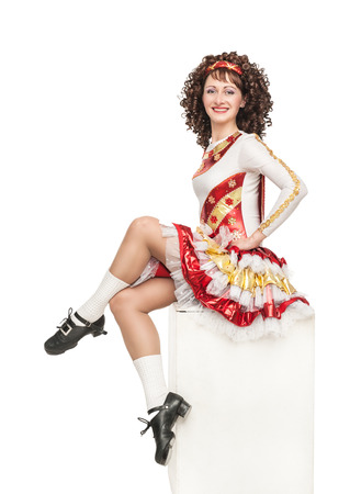 Young woman in irish dance dress, hard shoes and wig sitting on the stand isolated photo