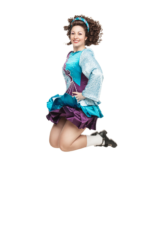 Young woman in irish dance dress and wig jumping isolated photo