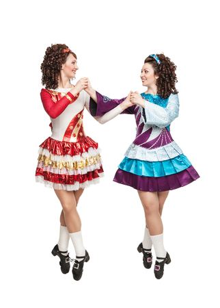 Young women in irish dance dresses, hard shoes and wigs posing isolated photo