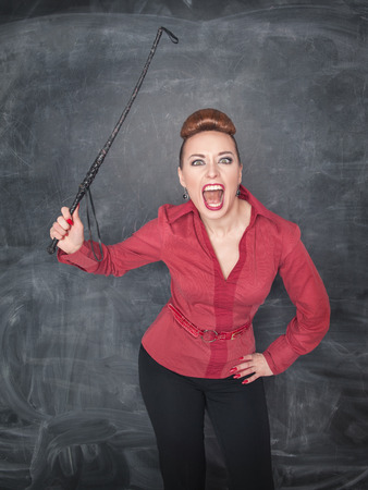 Angry screaming teacher with whip on her hand photo