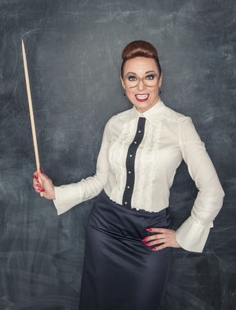 Crazy teacher with wooden pointer on the school blackboard background photo