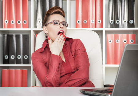 Beautiful business woman in glasses yawning at work photo