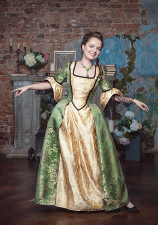 ruche: Smiling beautiful young woman in green and golden medieval dress dance