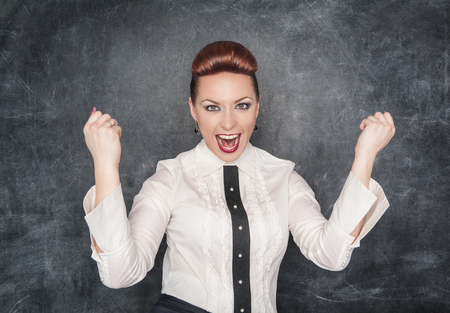 Beautiful business woman celebrating success on the blackboard background photo