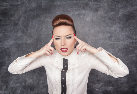 Beautiful woman with headache on the blackboard background photo