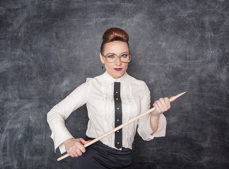 Strikte leraar met houten aanwijzer op zoek naar iemand