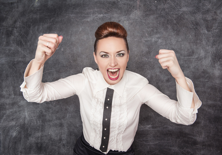 Angry screaming woman on the blackboard background photo