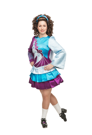 Young woman in irish dance dress, hard shoes and wig posing isolated photo