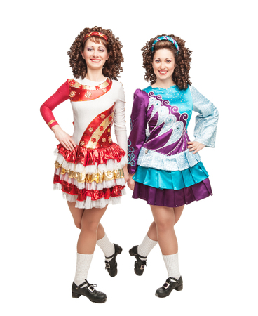 Irish dancers in hard shoes and wigs posing isolated photo