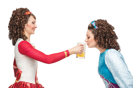 Two Irish dancers in the wigs drinking beer isolated photo