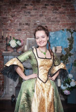 middeleeuwse jurk: Glimlachende mooie jonge vrouw in groene en gouden middeleeuwse jurk