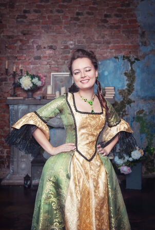 Beautiful young woman in green and golden medieval dress winking photo