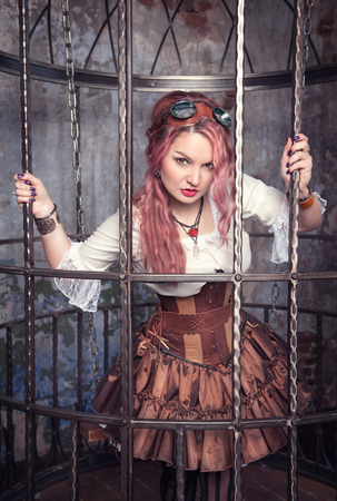 Beautiful steampunk woman with pink hair standing in the metal cage photo