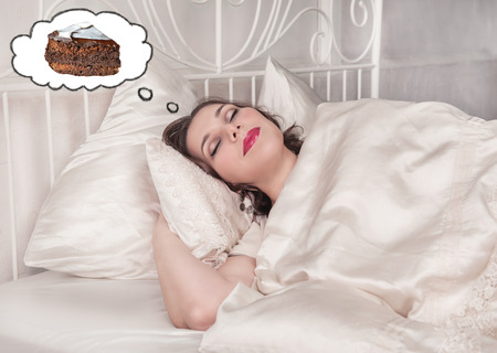 Beautiful plus size woman sleeping in the bed dreaming about cake photo