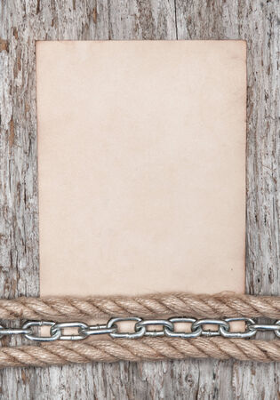 Old paper and metal chain on the old wooden background photo