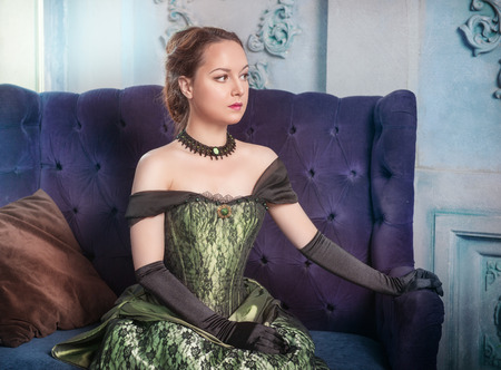Beautiful young woman in green medieval dress on the sofa photo