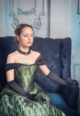 ruche: Beautiful young woman in green medieval dress on the sofa Stock Photo