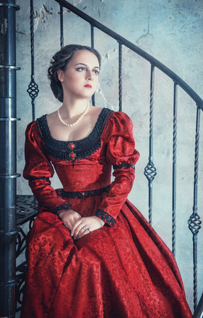 Beautiful young woman in red medieval dress on the stairway photo