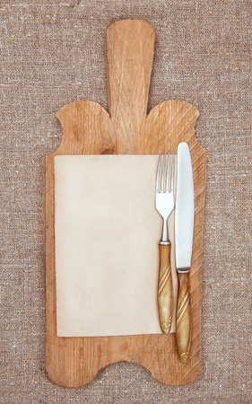 Old wooden kitchen board with aged paper, fork and knife on the burlap textile  photo