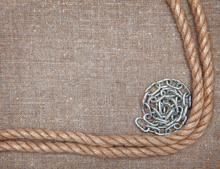 convolute: Metal chain, rope on the burlap textile background