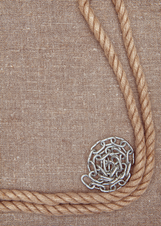 convolute: Metal chain and rope on the burlap textile background