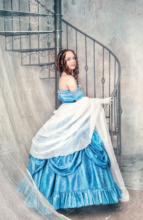 Beautiful young woman in blue medieval dress near the stairway photo
