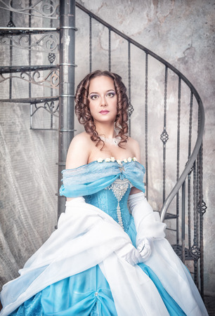 ruche: Beautiful young woman in blue medieval dress near the stairway Stock Photo