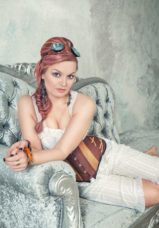 Beautiful steampunk woman with pink hair and trousers on the sofa photo