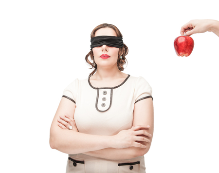 Blindfold beautiful brunette plus size woman temptating with apple isolated photo