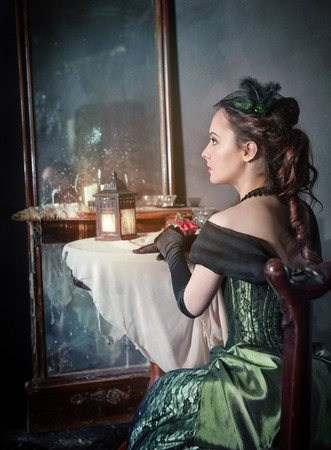 Joven y bella mujer en la medieval verde sesión vestido cerca del espejo