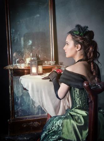 Mooie jonge vrouw in groene middeleeuwse jurk zitten in de buurt spiegel