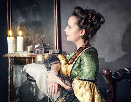 Beautiful young woman in green medieval dress sitting near mirror Reklamní fotografie