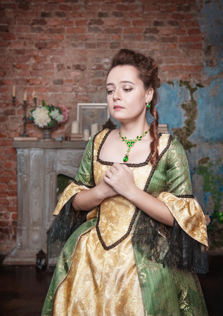 Sad beautiful young woman in green medieval dress photo