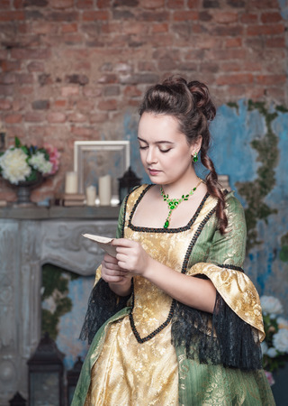 Beautiful young woman in green medieval dress reading letter photo
