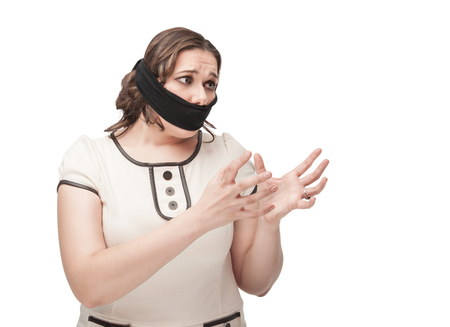 silenced: Beautiful brunette plus size woman gagged stretching hands to something isolated
