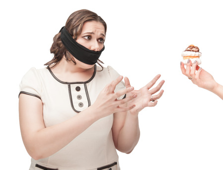 Beautiful brunette plus size woman gagged stretching hands to pastry isolated photo