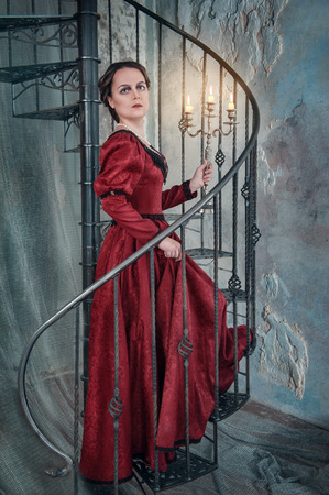 ruche: Beautiful woman in medieval dress with candelabrum on the stairway Stock Photo