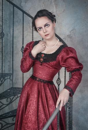 abito medievale: Bella giovane donna in rosso vestito medioevale sulla scalinata Archivio Fotografico