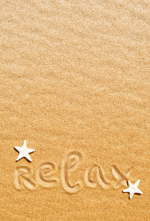 Summer background. Word relax and seashells on the sand photo
