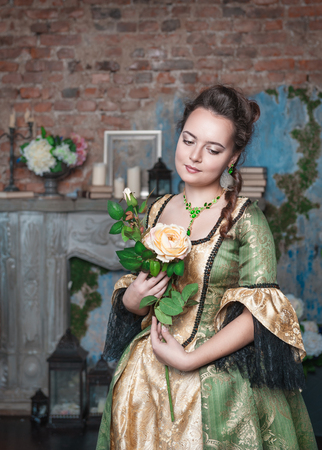 ruche: Beautiful young woman in green and golden medieval dress with flower