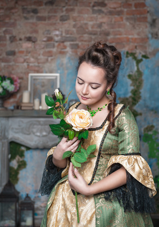 Beautiful young woman in green and golden medieval dress with flower photo