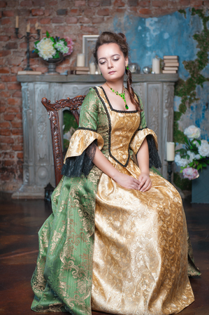 ruche: Beautiful young woman in green and golden medieval dress sitting on the chair