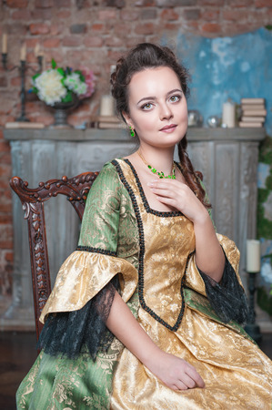 Beautiful young woman in green and golden medieval dress sitting on the chair photo