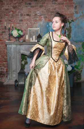 Beautiful young woman in green and golden medieval dress afraid photo