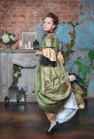 Beautiful young woman in green and golden medieval dress dancing photo